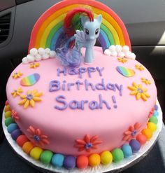 "Sarah's ""my little pony"" theme birthday cake. Easy to to - just stick a pony on top which the birthday girl can keep & make flowers and rainbow coloured balls. The rainbow was the hardest part - it's attached to cardboard & needed support from behind."