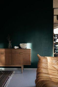 Le canapé Togo en cuir marron camel qui ressort de ce mur bleu vert en clin d'oeil a cette console commode buffet années 50.