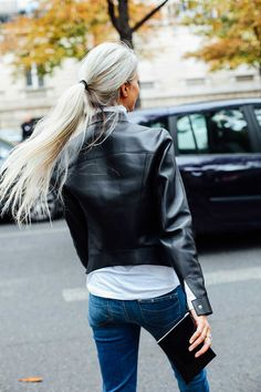 Jeans with a black leather moto and ponytail.
