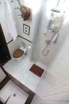<b>All-In-One Awesome</b><br /><br /> The shower is incorporated right into the greater overall space in this diminutive bathroom. White 1x1 inch tile is used on both the floor and walls throughout to bring it all together, while a dark wood counter, bath mat and toilet seat bring warmth to the room.