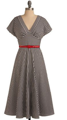 The basic lines of this dress— v-neck, shaped midriff, and flared skirt— can be achieved with a pattern like Vogue 8727. Don't miss the kimono sleeve extension and wider neck band.