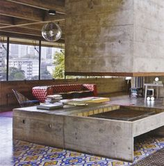 Designed in 1969 by PAULO MENDES DA ROCHA, who went on to win the Pritzker Architecture Prize in 2006 and is now 83 years old, the house is a stellar example of Paulista, the local school of brutalism that he championed in the 1950's and '60's. Laid into the floor's tinted-cement tile, matting leads from the front door to the dining area's artwork by Alexandre Orion.