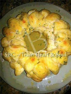 PULL-APART GARLIC BREAD  SUPER EASY! QUICK! DELISH!!!  INGREDIENTS: 1 can (or 2) of Grand sized biscuits 1/2 stick of REAL butter Garlic powder Parsley  DIRECTIONS: Cut each biscuit into quarters. Place quartered biscuits in a large bowl. In another small bowl melt butter in the microwave. Add enough garlic and parsley to taste great. Stir seasoned butter mixture. Pour butter over biscuit quarters. Toss until well coated. Place butter coated biscuit quarters in a Bundt pan, piece by ...
