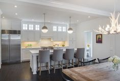 A pair of Thomas O'Brien Hicks Pendants hang over a white kitchen island topped with marble fitted with a sink and vintage faucet lined with gray velvet stools, Restoration Hardware 1940s French Barrelback Fabric Stools.