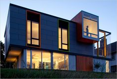 Wisconsin LEED Platinum home with colorful window details, CBF concrete board cladding, and vertical wood of some kind.