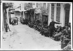 German prisoners of war at Canea, Crete, during World War 2. Shows a row of German paratroopers under New Zealand guard lined up along one side of a street. Some are wounded. Photograph taken circa 1941. Photographer unidentified. National Library of New Zealand.