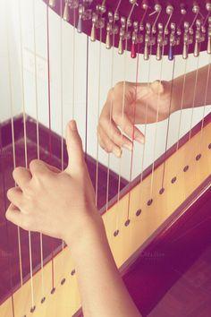 Closeup of a woman playing the harp by mutita.narkmuang on Creative Market