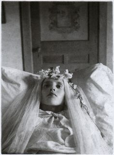 A particularly beautiful young girl laid out in the parlor, circa 1910. It was not uncommon to dress dead young girls in what looked like a wedding veil and dress to symbolize their purity as they go to 'meet God'.