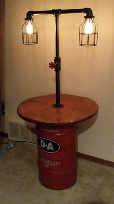 Antique oil barrel, pipe lamp, Tesla lights with a valve dimmer switch end table. Made by my husband! More