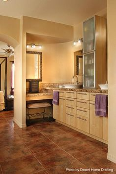 Women would certainly love this bathroom setup with Jack and Jill sinks and a tan-seated vanity area. Open area to bedroom.