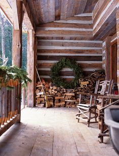 Rustic Christmas porch, evergreens, huge simple wreath, wood pile