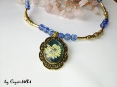 """The """"Golden Flower"""" necklace is handmade with dried natural flowers preserved in glass cabochon, deep blue glass beads and decorative metallic accessories, antique gold. See more of my creations on Golden Flower, Flower Necklace, Deep Blue, Antique Gold, Jewerly, Glass Beads, Metallic, Antiques, Natural"""