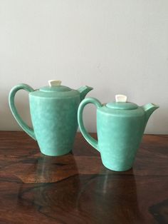 An absolutely beautiful pair of Art Deco Streamline Poole Pottery Coffee Pots, dating from between 1952 and 1955 based on the base stamp. This beautiful flowing design with its distinctive wedge-shaped handle originated in the 1930s and was the brainchild of John Adams. Originally only five twintone colors were released in the 1930s, these pots being an example of C65, Magnolia and Shagreen, (and in my mind the most beautiful). With a soft matt lustre - described as vellum they are both…