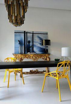 Sala de jantar com mesa minimalista consola lustre contemporâneo e cadeiras amarelas brilhantes