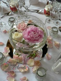 I think a floating peony (and roses perhaps) in central fishbowl surrounded by candles in glass votives with scattered rose petals, on a mirror tile would be an inexpensive table centre that has day and evening appeal plus fits the wedding theme...