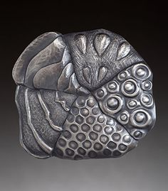 Nancy Megan Corwin: Conjoined, Brooch in sterling silver, chasing and repousse. Approx 2 7/8 x 2 5/8.