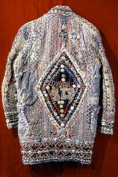 MAN'S 'DIAMOND SIS' COAT/ Charlie Logan (1893–1984), 1978–1984, various fabrics covered with yarn and thread embroidery, trimmed with buttons, coins, tassels, and American flags, with metal and rhinestones, 32 × 17 ½ in., collection Philadelphia Museum of Art, 125th Anniversary Acquisition, gift of the Friends of the Philadelphia Museum of Art and partial gift of Kate and Ken Anderson, 1998. Photo © Philadelphia Museum of Art.