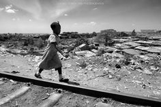 """Africa where are you going ... Makadare Slum Nairobi. From my series: """"Beauty In Hell - Beauty over Drama"""". #beautyinhell. A young girl playing on the railway that runs through Kibera (the second largest slum in the world - Nairobi). All you can see in the background is Kibera with over one million people. While I was taking this picture my mind kept thinking about what kind of future awaits the African countries. ---------------------------------- WEBSITE: www.tonycorocher.com FB…"""