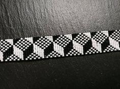 Handgeweven kralenarmband met Miyuki kralen 11/0 in zwart en wit. Lengte 15 cm met zilverkleurige sluiting en een verlengketting van 6 cm. Breedte: 2 cm.