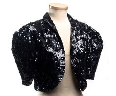 """This short evening jacket is completely covered with shiny black sequins, and dates to around 1931. What a glittery way to accessorize a svelte evening gown! It bears the label: """"Hattie Carnegie, Inc. / Little Salon,"""" and was probably part of this American designer's ready-to-wear line. The label may refer to Carnegie's new store in Manhattan, opened in June 1931."""