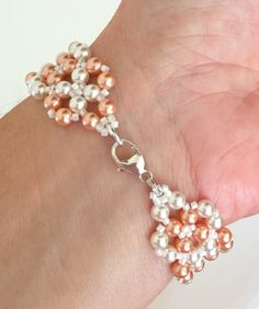 A classic and elegant style, this Swarovski pearl bracelet is created with lovely white and peach colored faux pearls and white acrylic beads. The pearls and beads are woven and braided into this lovely crisscross design that will be a showstopper on your wrist. This bracelet will complement any attire and can be worn for any occasion. Fashioned with a moderately sized sterling silver lobster claw clasp, it is easy to take on and off.  ***SEE SHOP BANNER FOR CURRENT SALES AND SPECIALS…