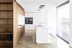 berlin - penthouse - kitchen - white -built-in - cabinet - drawer - herringbone - oak - floor - walnut-panell - elevator core - wohnung - erschließungskern - küche - einbaumöbel - walnuss - weiß - kücheninsel - herd - spüle - wohnbereich - regal
