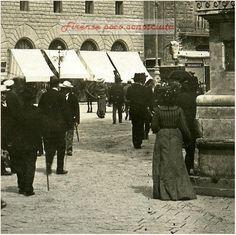 Passeggiare con i vecchi fiorentini, presi di spalle, in Piazza della Signoria nel 1908. La statua di Cosimo non ha nessuna barriera ed i negozi vengono riparati dal sole e dalla pioggia dalle lunghe tende. — a Firenze.