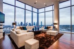 A plush, brown shag rug grounds this penthouse living area. White leather furnishings offer comfortable and stylish seating set against a backdrop of downtown Dallas.