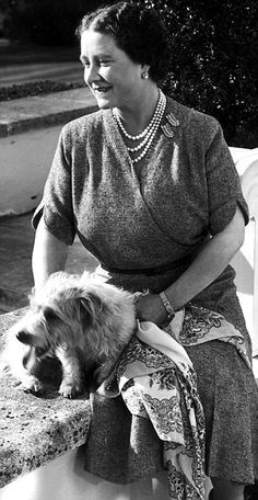The Queen Mother cuddling her little shaggy Terrier.