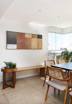 Decoração de apartamento para uma família. Na varanda, quadro, obra de arte, banco de madeira, plantas, mesa de jantar de madeira, cadeira de madeira.    #decoracao #decor #details #casadevalentina
