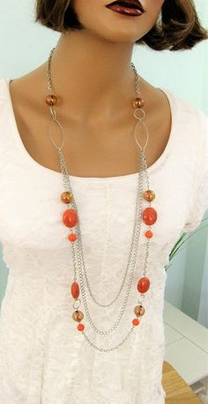 Long Beaded Orange Multi Strand Necklace handmade by Ralston Originals. This necklace is made with large chunky orange acrylic beads. The acrylic beads make this necklace lighter weight. The necklace includes multi strands of 3 different silver chains, and large silver metal rings. This orange necklace is about 40 inches long. This is a limited edition necklace. This Multi Strand Necklace is ready to send to you today. I carefully package it and send it in a gift box, making it easy and…