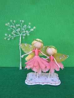 Mom and daughter flower fairy dolls. Mom and daughter are standing by each other on a thin handpainted wooden base of 2x3 inches. Their dresses are made from coral flower petals. They have lightly sparkling wings and pearl shoes. Each blond hair is adorned with a green crown. Mom is