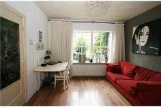 Ruime L-vormige woonkamer voorzien van mooie laminaat vloer met schouw en openslaande deuren naar de tuin. De woonkamer is in 2006 uitgebouwd en heeft veel daglichttoetreding door de vele gezellige ramen.