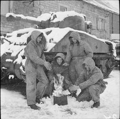 A Sherman tank crew of 29th Armoured Brigade 11th Armoured Division warm themselves around a petrol stove in the village of Mesnil-Eglise near Dinant in Belgium 4 January 1945.