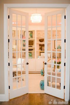Book shelves and French doors - yes! White chair and sleek light fixture - double yes!