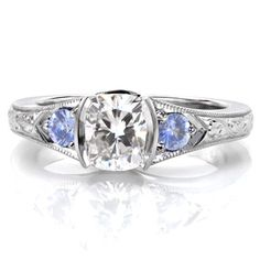 This beautiful engagement ring is a Knox Jewelers custom engagement ring created in Minneapolis, Minnesota. This ring's cushion cut center diamond is trimmed on either side with pale blue sapphires. The band also features hand engraving in a scroll pattern.
