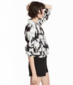 Black/patterned. Bomber jacket in soft fabric. Small stand-up collar, concealed snap fasteners at front, and welt side pockets. Wide ribbing at cuffs and