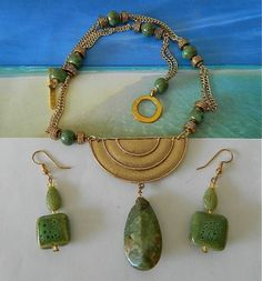 "This  necklace-earrings  set  features  an  unusual  shaped  gold tone  pendant,  a  jasper  teardrop  bead  and  green  ceramic  beads.                Necklace  measures  18.5""  with  gold  tone  tog"
