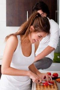 Frau schneidet Gemüse in der Küche