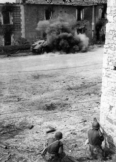 American soldiers firing with a bazooka at a German Panzer tank. 1944-1945.