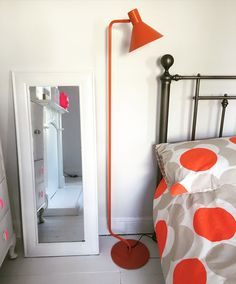 White bedroom. Orange lamp by Made.com Bedding by Orla Kiely.