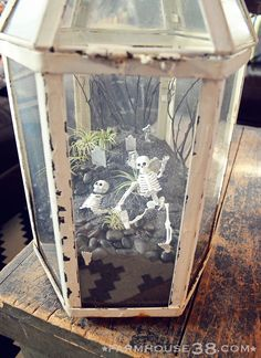 A Halloween terrarium featuring tiny skeletons, a tiny graveyard