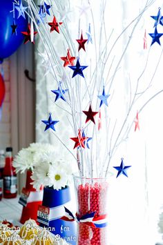 Patriotic Centerpiece ~ glass vase filled with some twigs painted white and red/white/blue stars hanging from the branches. This in center surrounded by rice filled jars