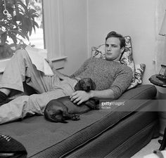 Portrait of American actor Marlon Brando (1924 - 2004) as he reclines on a bed with a pet dachshund and an open film script while on a visit to his grandmother's house, Van Nuys, California, October 1949.