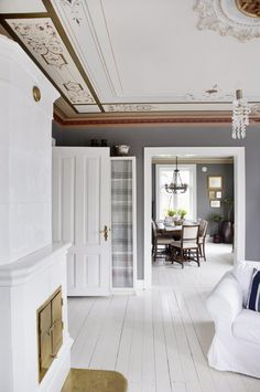 HERSKAPELIG: Denne stuen har mange fine detaljer, som takmaling, rosetter, kakkelovn og gamle dører. Alle bidrar til det herskapelige preget i rommet. Det hvitmalte gulvet og den nøytrale gråfargen på veggen lar detaljene skinne.