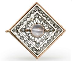 A Jeweled and Enameled Gold and Platinum Brooch  By Fabergé, with the workmaster's mark of August Holmström, St. Petersburg, 1896-1908 Diamond-shaped, centering a cabochon moonstone within a wirework radiating surround set with rose-cut diamonds, within two opaque white enamel frames enclosing a band of rose-cut diamonds, marked on pin and pin guard