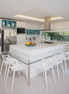 Modern white kitchen with teal cubbies and mix of open and closed storage