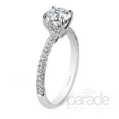 Parade Design: A diamond enhanced bloom embraces the center diamond of this Lyria engagement ring finished with a gracefully contoured band.