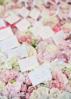 Escort cards are elegantly arranged atop tightly packed flower in shades of pink.