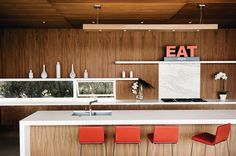 Walnut veneer clads the cabinets, walls, and ceiling, as well as the custom light fixture that hangs over the island.